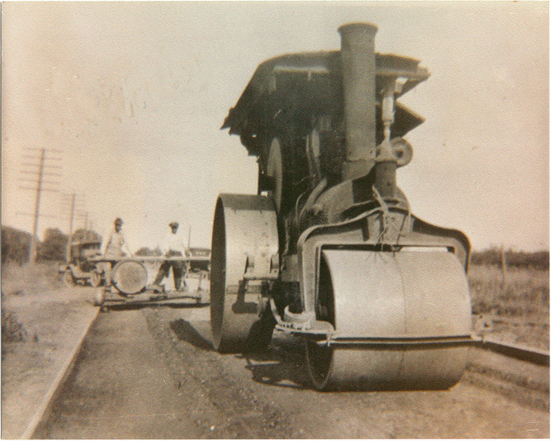 an old sepia toned back and white image of an asphalt roller