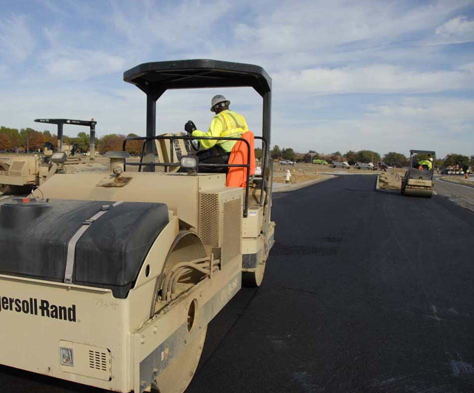 an image of a steam roller flattening some asphalt