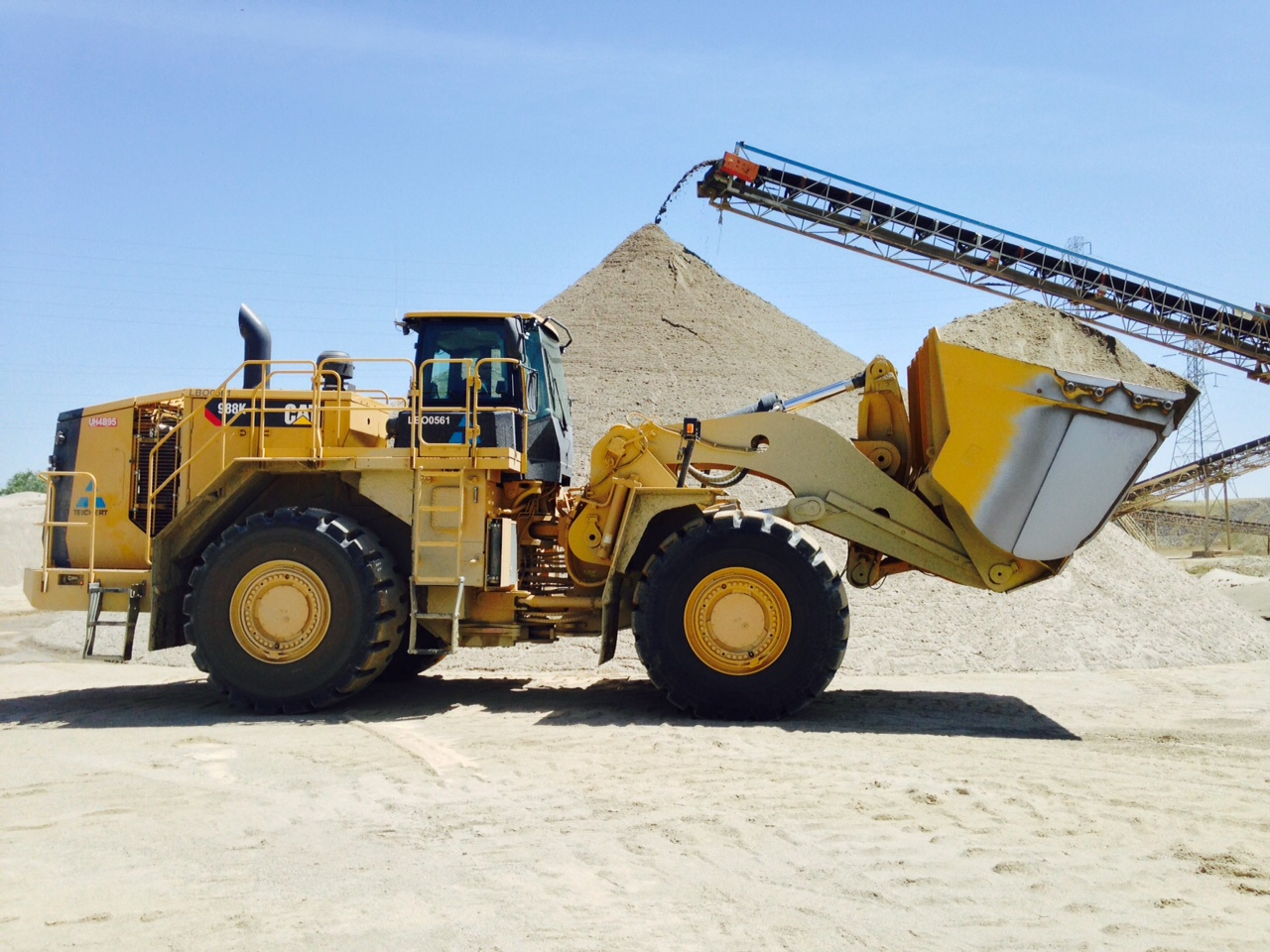 Photo of a loader with pile of aggregate in the background