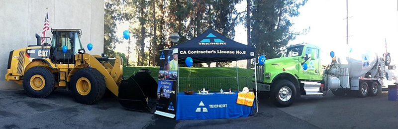 an image of a Teichert recruiting kiosk at an event with trucks in the background