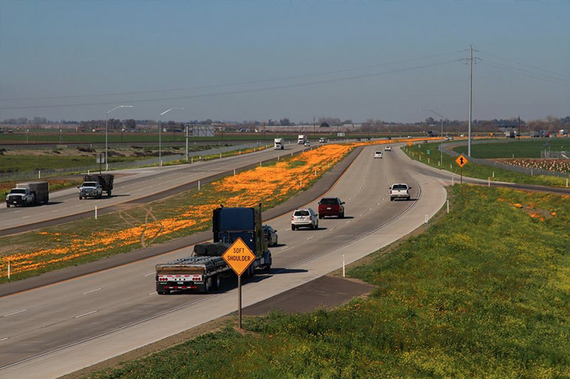 a photograph of a highway with cars driving on it