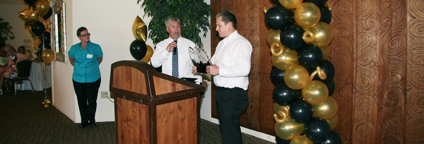 an image of a man presenting an award to another man in a convention center