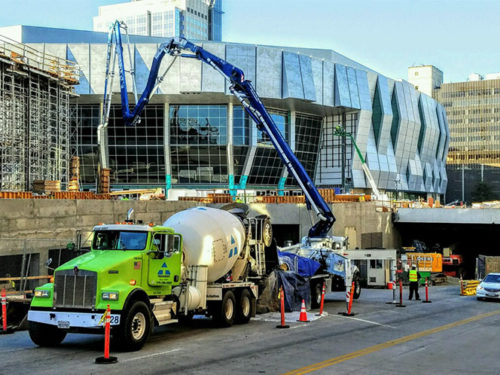 a landscape photo of a green Teichert cement truck pouring cement at the site of the new Golden One Sacramento Kings Arena