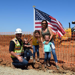 image of teichert employee with family standing in front of american flag