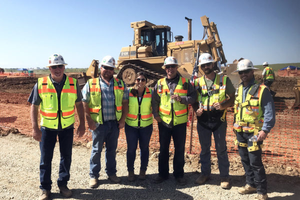 an image of 6 Teichert employees standing together at a job site all wearing safety equipment and posting for a photograph in front of some large construction equipment