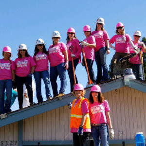 Women Build team standin on roof all wearing pink shirts