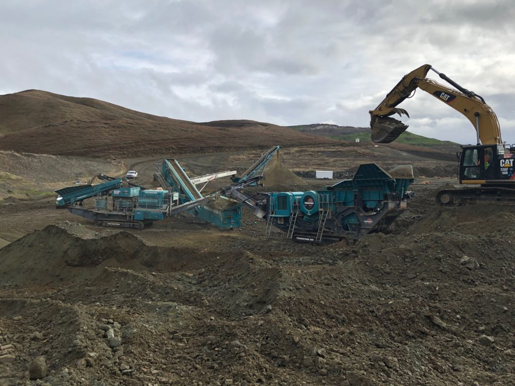 an image of large construction equipment clearing dirt from a landscape